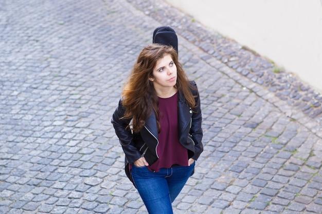 Poważna ładna kobieta spaceru z gitarą na ulicy
