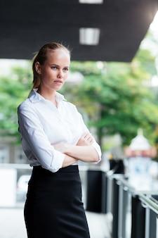 Poważna ładna kobieta stojąca z założonymi rękoma na zewnątrz