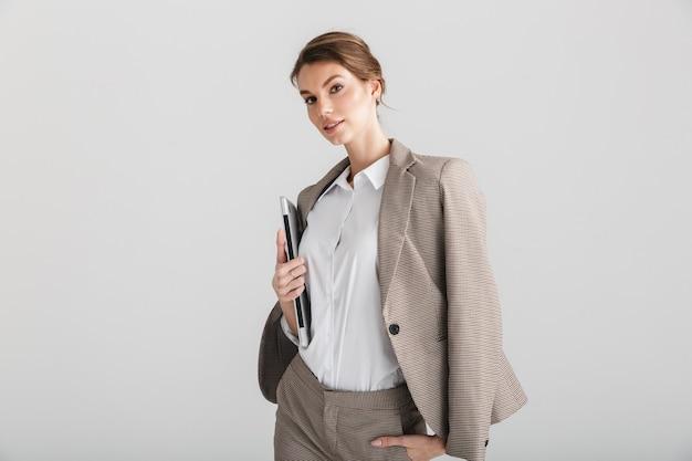 Poważna ładna kobieta w formalnym garniturze pozuje z laptopem w aparacie na białym tle na białym tle