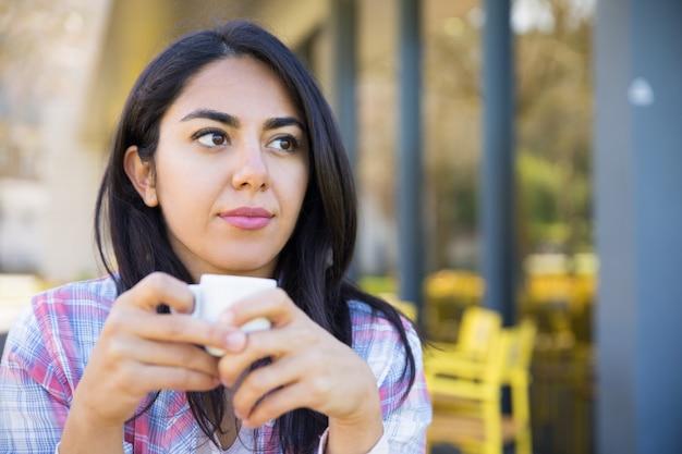 Poważna ładna młoda kobieta cieszy się pijący kawę w kawiarni