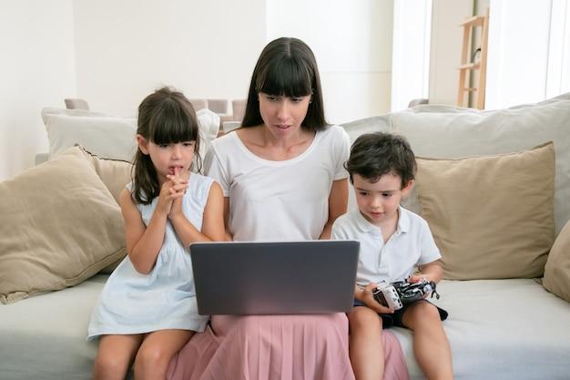 Poważna mama i dwoje zmartwionych dzieci oglądają film na laptopie w salonie.