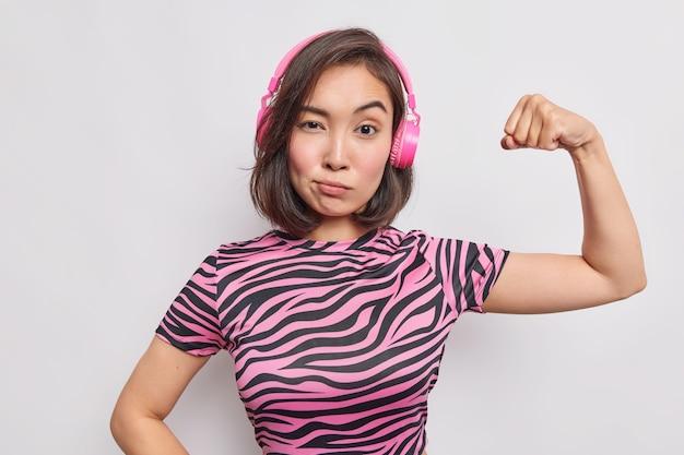 Poważna młoda azjatka zdeterminowana, wyraz twarzy unosi ramię pokazuje biceps czuje się silny, słucha muzyki przez bezprzewodowe słuchawki, ubrana w pasiastą koszulkę na białym tle nad białą ścianą