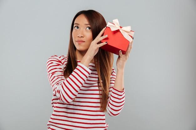 Poważna młoda azjatykcia dama stoi odosobnionego mienie prezent.