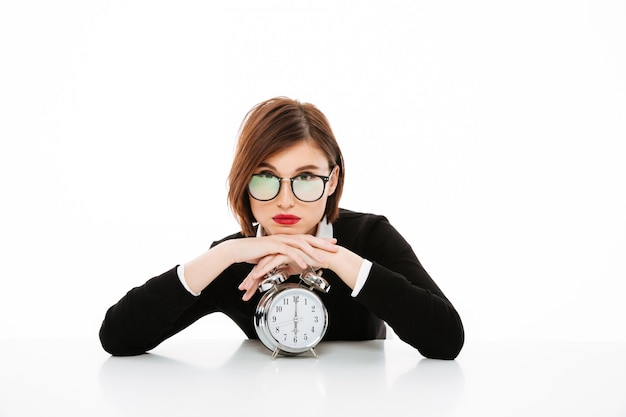 Poważna młoda biznesowa dama jest ubranym szkła z budzikiem