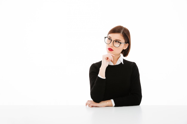 Poważna młoda biznesowa dama jest ubranym szkła