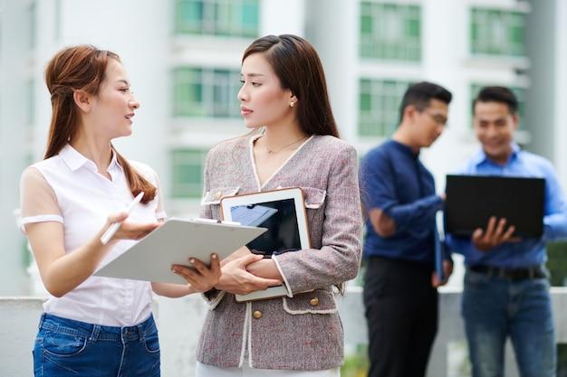 Poważna młoda bizneswoman azjatyckiego patrząc na kolegę ze schowka, wyjaśniając jej kreatywne pomysły