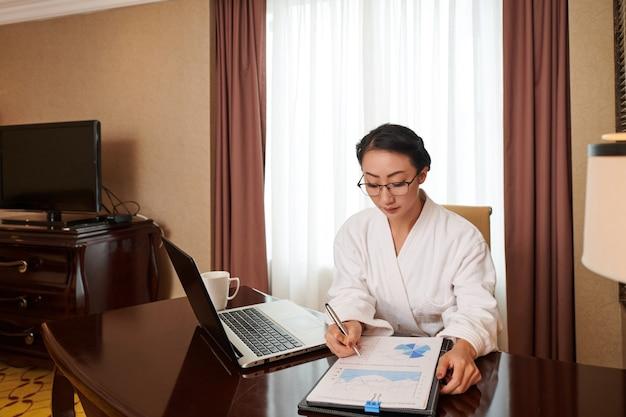 Poważna młoda bizneswoman w szlafroku analizująca raport sprzedaży, siedząc przy stole w pokoju hotelowym