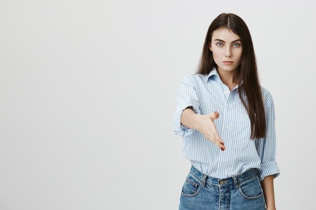Poważna młoda bizneswoman wyciągnąć rękę do uścisku dłoni