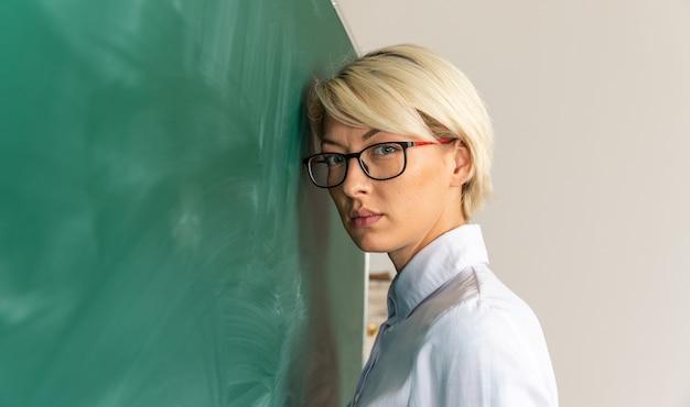 Poważna młoda blondynka nauczycielka w okularach w klasie, stojąc przed tablicą w widoku profilu, pochylając głowę na tablicy, patrząc na kamery