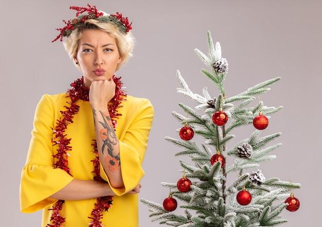 Poważna młoda blondynka ubrana w świąteczny wieniec i girlandę ze świecidełek na szyi stojącą w pobliżu ozdobionej choinki patrzącą trzymając rękę pod brodą na białym tle na białej ścianie