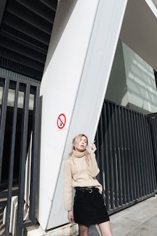 Poważna młoda blondynki dama z papierosem