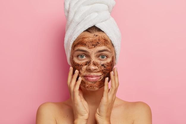 Poważna młoda dama nakłada peeling kawowy na twarz, peelinguje skórę, usuwa pory, dotyka dłońmi policzków, ma nagie ciało