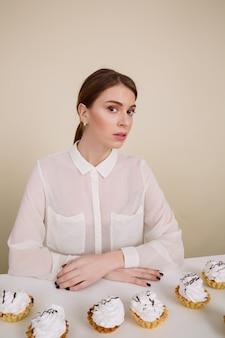 Poważna młoda dama pozuje podczas gdy siedzący blisko babeczek