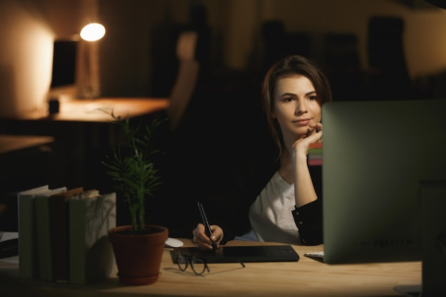 Poważna młoda dama projektantka za pomocą komputera i tabletu graficznego.