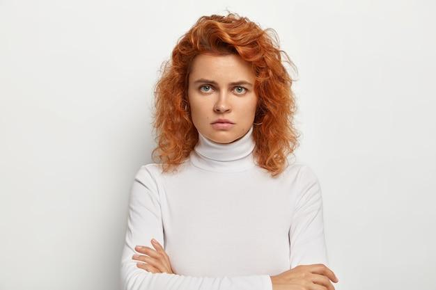 Poważna młoda dama z kręconymi rudymi włosami, niezadowolona z czegoś, patrzy ze złością, trzyma ręce skrzyżowane, nosi biały swobodny golf, obrażona głupim pytaniem, pozuje sama w domu.
