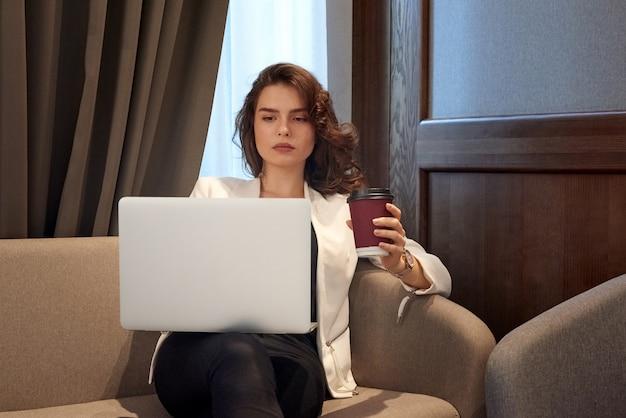 Poważna młoda dziewczyna pracuje na laptopie i pije kawę