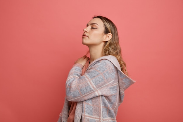 Poważna młoda dziewczyna stoi w widoku profilu, trzymając rękę na ramieniu z zamkniętymi oczami