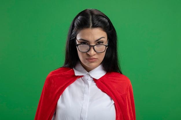 Poważna młoda dziewczyna superbohatera kaukaski w okularach na białym tle na zielonej ścianie z miejsca na kopię