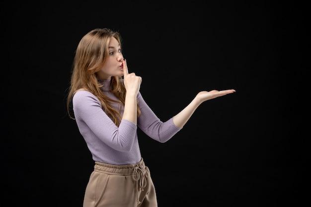 Poważna młoda dziewczyna wskazująca coś na lewą stronę i robiąca gest ciszy w ciemności