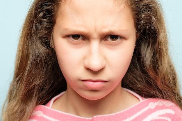 Poważna młoda dziewczyna z gniewnym, niezadowolonym spojrzeniem i zmarszczonymi brwiami. koncepcja emocji i uczuć.