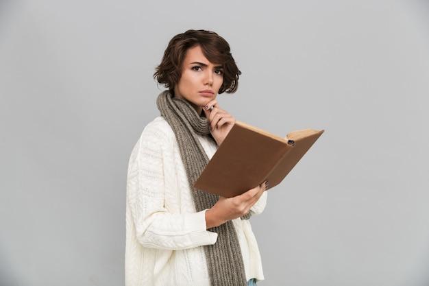 Poważna młoda kobieta jest ubranym szalika czytelniczą książkę.