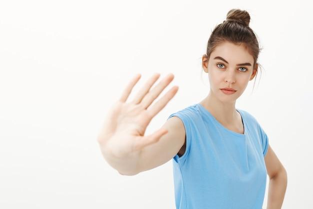 Poważna młoda kobieta mówi, żeby przestała, mówiąc nie, wyciągnęła rękę w geście zakazu, ostrzeżenia lub dezaprobaty