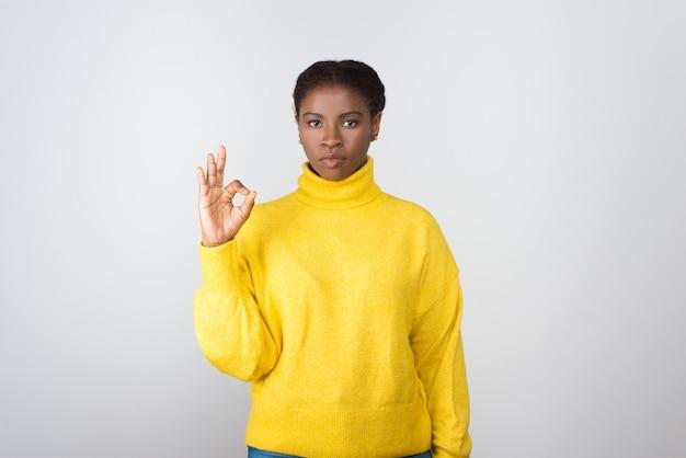 Poważna młoda kobieta pokazuje ok znaka