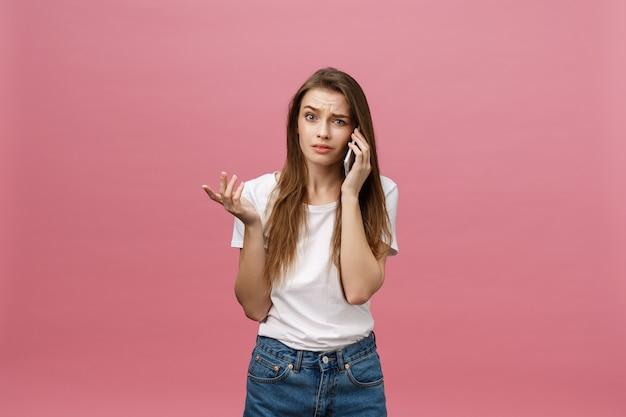 Poważna młoda kobieta rozmawia przez telefon