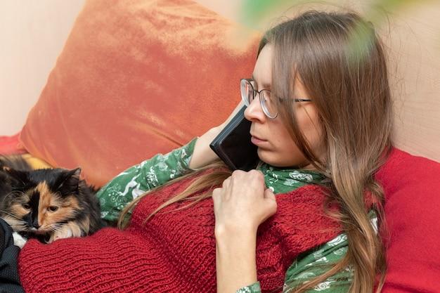 Poważna młoda kobieta rozmawia ze smartfonem w jej rękach, siedząc na kanapie ze swoim kotem w domu.