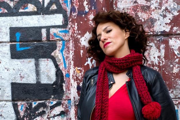 Poważna młoda kobieta stojąca przy ścianie graffiti na ulicy.