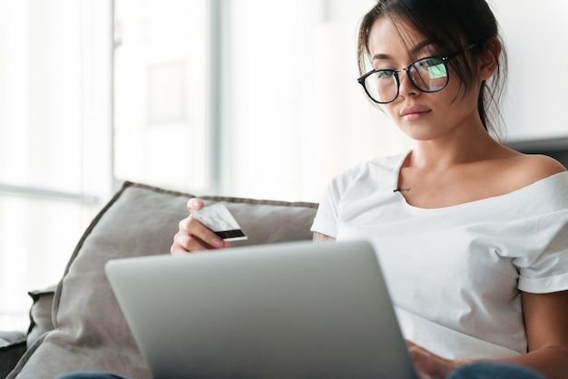 Poważna młoda kobieta trzyma kartę debetową używać laptop.