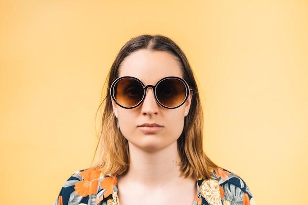 Poważna młoda kobieta ubrana w kwiecistą koszulę i duże okrągłe okulary przeciwsłoneczne