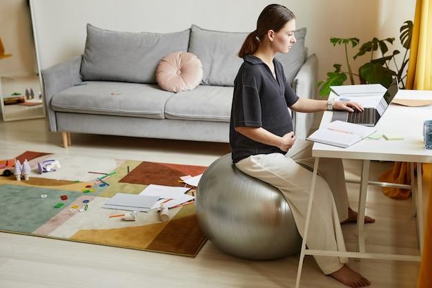 Poważna młoda kobieta w ciąży siedzi na fitball w salonie z bałaganem na dywanie i korzysta z laptopa podczas pracy w domu