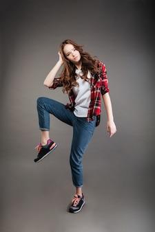 Poważna młoda kobieta w kraciastej koszula i taniec dżinsach