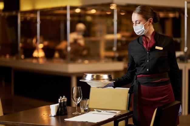 Poważna młoda kobieta w masce pracująca w restauracji
