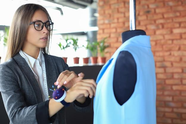 Poważna młoda kobieta w okularach przy użyciu igieł do szycia kurtki na manekinie, stojąc w swoim warsztacie.