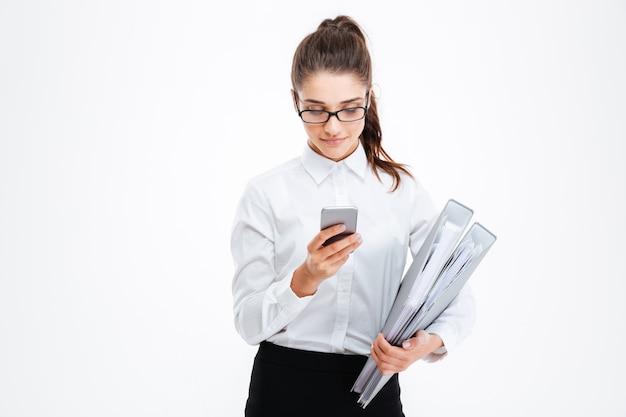 Poważna młoda kobieta w okularach trzymająca foldery i używająca smartfona na białej ścianie