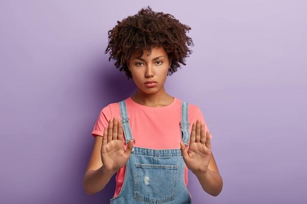 Poważna młoda kobieta z afro pozowanie w kombinezonie