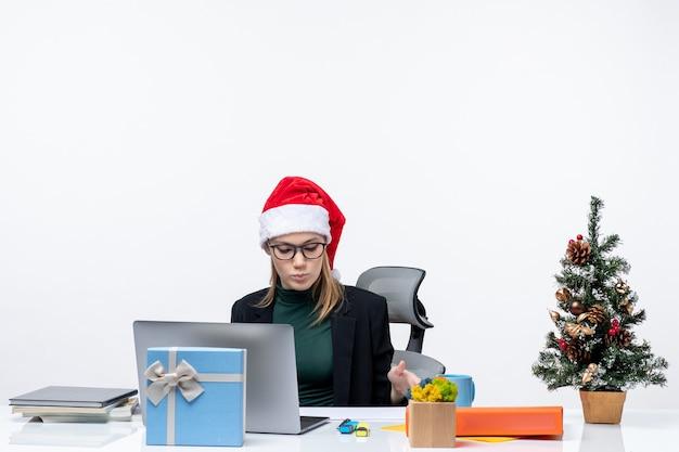 Poważna młoda kobieta z czapką świętego mikołaja i okularami siedzi przy stole z choinką i prezentem w biurze