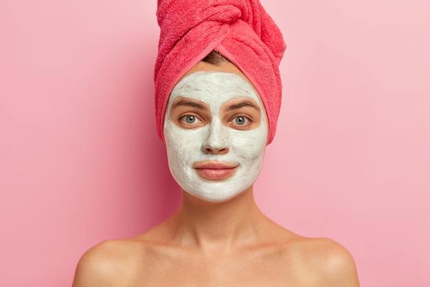 Poważna młoda kobieta z glinkową maseczką na twarz, nosi owinięty ręcznik, odżywia skórę witaminami