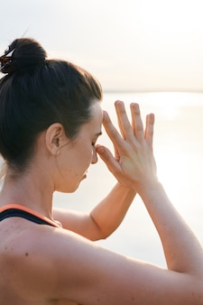 Poważna młoda kobieta z kokami do włosów, skupiona na umyśle, trzymając oczy zamknięte i opierając głowę na palcach na zewnątrz