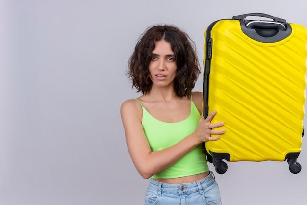 Poważna młoda kobieta z krótkimi włosami w zielonej bluzce, trzymając żółtą walizkę na białym tle