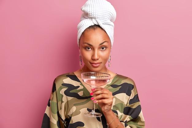 Poważna młoda kobieta z zadbaną cerą zdrową skórą wygląda pewnie trzyma kieliszek koktajlowy ma manicure nosi domowe ubrania odizolowane na różowej ścianie. impreza w domu.