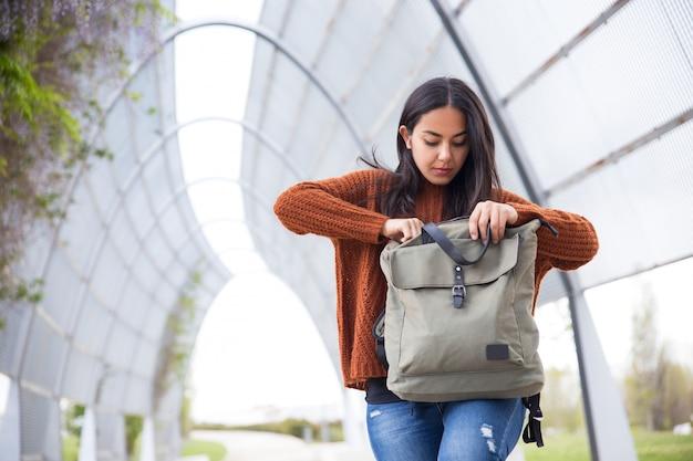 Poważna młoda kobieta znajduje telefon w torbie na zewnątrz
