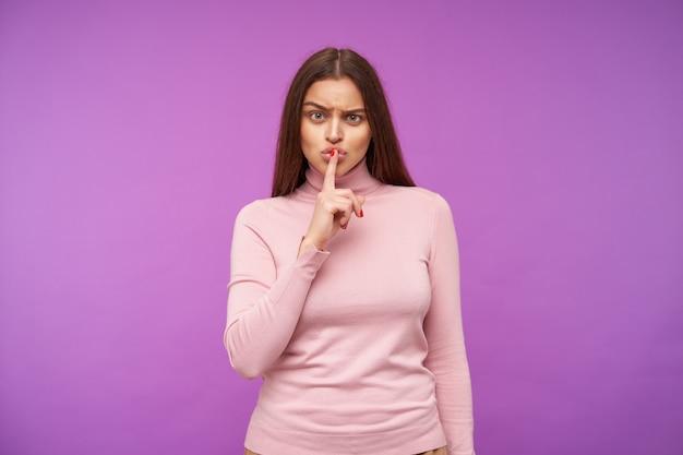 Poważna młoda ładna brązowowłosa kobieta z naturalnym makijażem marszczy brwi, patrząc surowo z przodu, podnosząc rękę z gestem wyciszenia, pozując nad fioletową ścianą