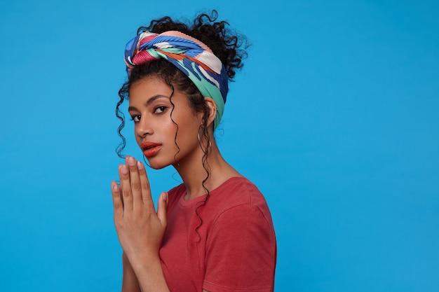 Poważna młoda ładna brunetka kobieta z przypadkową fryzurą, trzymając podniesione dłonie razem, patrząc zamyślony z przodu, odizolowane na niebieskiej ścianie