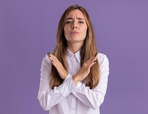 Poważna młoda ładna kaukaska dziewczyna krzyżuje ręce, gestykulując bez znaku