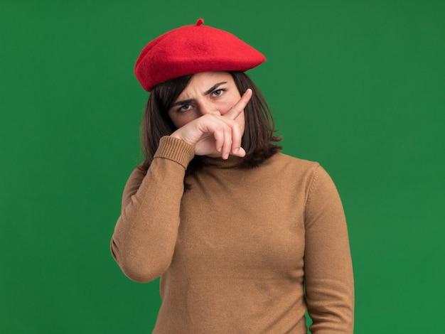 Poważna młoda ładna kaukaska dziewczyna w berecie kładzie rękę na nosie na zielonej ścianie z miejscem na kopię