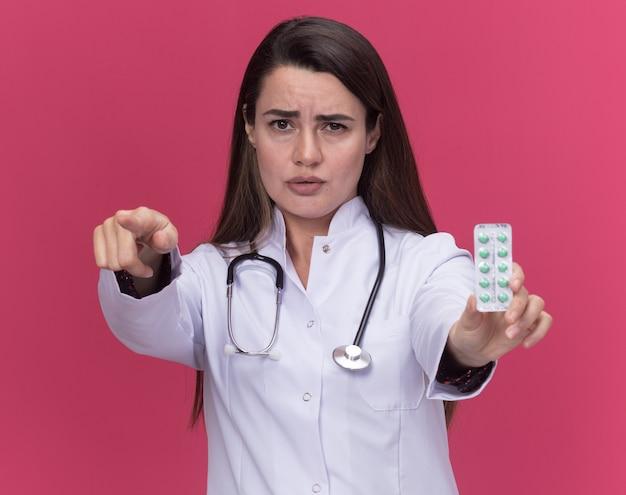 Poważna młoda lekarka w szacie medycznej ze stetoskopem trzyma paczkę leków i wskazuje na kamerę odizolowaną na różowej ścianie z kopią przestrzeni