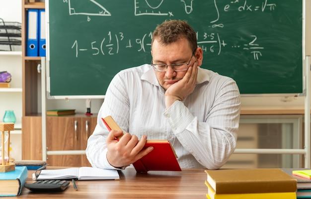 Poważna młoda nauczycielka blondynka w okularach siedzi przy biurku z szkolnymi narzędziami w klasie, czytając książkę trzymając rękę na twarzy